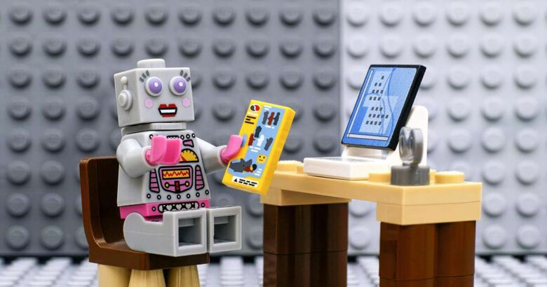 Lego robot minifigura con instructivo sentada frente el computador